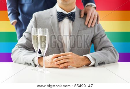people, celebration, homosexuality, same-sex marriage and love concept - close up of happy married male gay couple with sparkling wine glasses on wedding over rainbow flag background