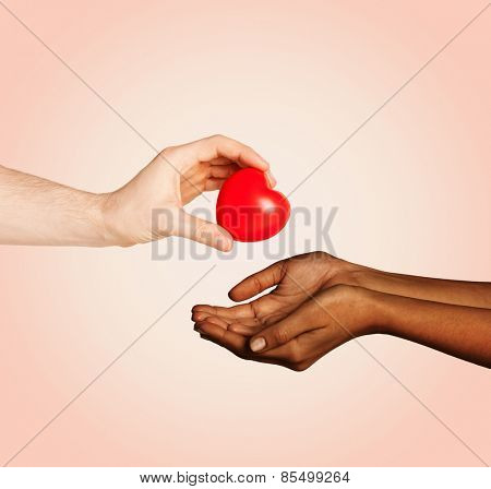 love, charity, valentines day, donation and international concept - close up of man hand giving heart to woman over beige background