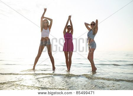 friendship, summer vacation, party, happiness and people concept - group of happy female friends dancing on beach
