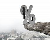 foto of cliffs  - Businessman hanging on cracked percentage sign with cliff and urban scene background - JPG