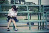 image of schoolgirls  - Cute Thai schoolgirl is sitting and reading on a stand in vintage color - JPG