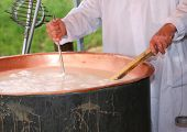 stock photo of temperature  - cheesemaker checks the temperature of the boiling milk in the pot for making cheese
