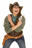 picture of pistols  - A cowgirl with her arms crossed laughing with a pistol on her shoulder - JPG