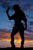image of pistols  - A silhouette of a woman with her pistol in the air looking down - JPG