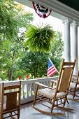 pic of rock star  - Comfortable wooden rocking chair on an outdoor patio with an ornamental white balustrade below the Stars and Stripes American flag to enjoy 4th July and Independence Day - JPG