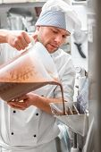 foto of confectioners  - Handsome confectioner in chef uniform producing ice cream with ice cream machine - JPG