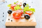 stock photo of black-cherry  - Selective focus on the front sliced cherry tomato and black olive - JPG
