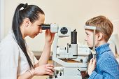 Постер, плакат: Optometry concept Female optometrist optician doctor examines eyesight of child boy in eye ophthalm