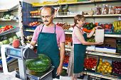stock photo of senior adult  - adult senior sale man with assistant in fruit vegetable market shopping store - JPG