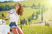 picture of scooter  - Young beautiful italian woman sitting on a italian scooter in Italy hills - JPG