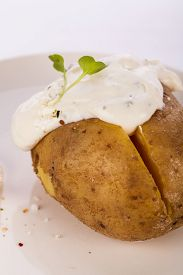 picture of endive  - Overhead view of a healthy oven baked jacket potato with sour cream sauce garnished with endive leaves and fresh herbs - JPG