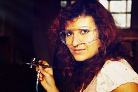 picture of airbrush  - A young woman painting with airbrush equipment and airbrush gun - JPG
