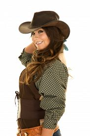stock photo of cowgirl  - A cowgirl with a big smile on her face looking to the side in her cowgirl hat and her holster on - JPG