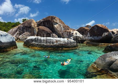 Family of mother and son snorkeling in turquoise tropical water among huge granite boulders at The Baths beach area major tourist attraction on Virgin Gorda, British Virgin Islands, Caribbean
