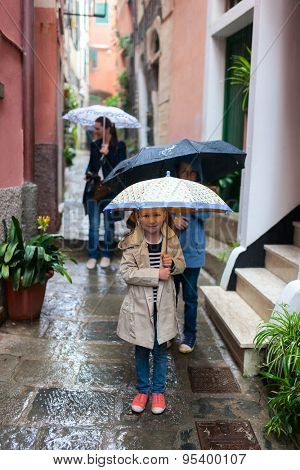 Family of mother and two kids at narrow street of Vernazza village in Cinque Terre on rainy day