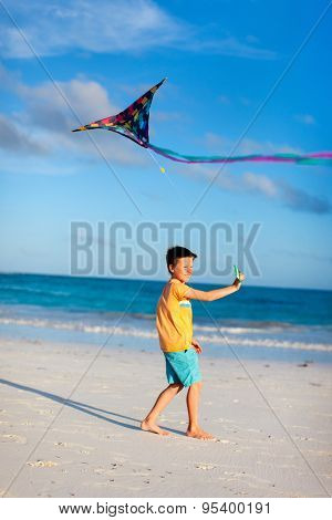 Little boy flying a kite on beach