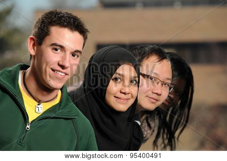 Group of four diverse ethnic students with focus on first woman