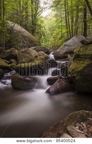 Long time exposure of water cascading over rocks in lush forest