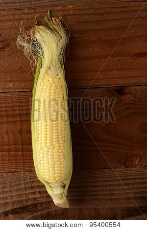 A single fresh picked and shucked ear of corn on the cob on a rustic wood table. The sweet corn is shot from a high angle in vertical format.
