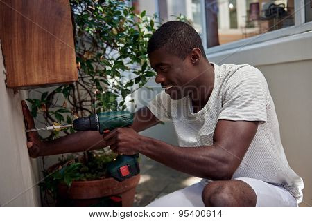 african black man using cordless battery drill for diy outdoor home improvements