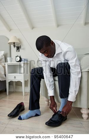 professional african black man getting ready for work putting formal smart shoes on for work in morning at home