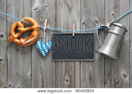 Message, beer mug and pretzel hanging on the clothesline against wooden board. Background for Oktoberfest