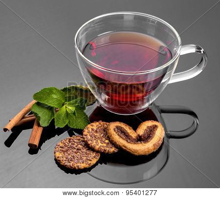 Cup of tea with mint, cinnamon and cookies.