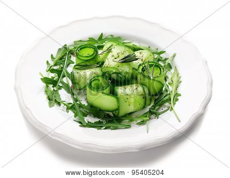 Plate of green salad with cucumber, arugula and rosemary isolated on white