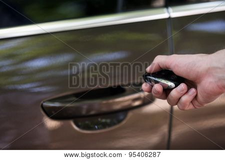 Hand presses on remote control car alarm systems