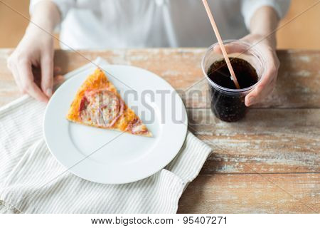fast food, people and unhealthy eating concept - close up of woman hands with pizza and coca cola drink sitting at table