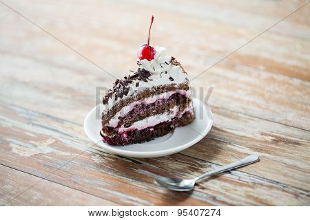 food, junk-food, culinary, baking and holidays concept - piece of delicious cherry chocolate layer cake on saucer with spoon on wooden table
