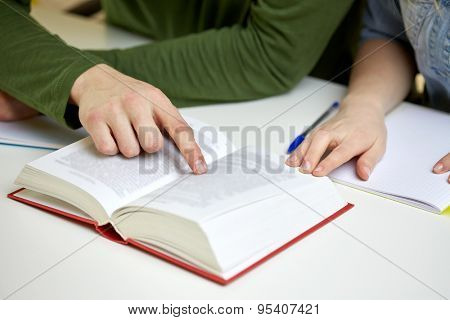 education, people and school concept - close up of students hands reading textbook or book at school
