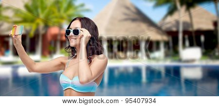 people, technology, summer vacation and travel concept -young woman in bikini swimsuit and sunglasses taking selfie with smatphone over swimming pool, bungalow at hotel resort background