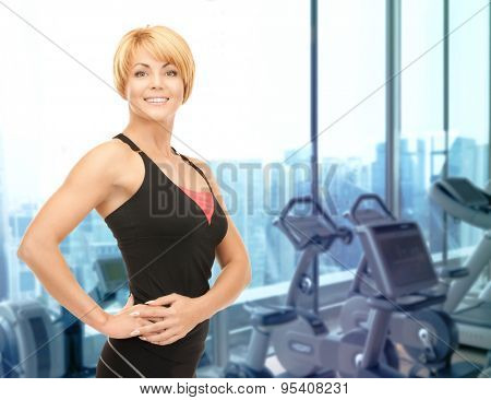 people, fitness and sport concept - happy woman fitness instructor over gym machines background