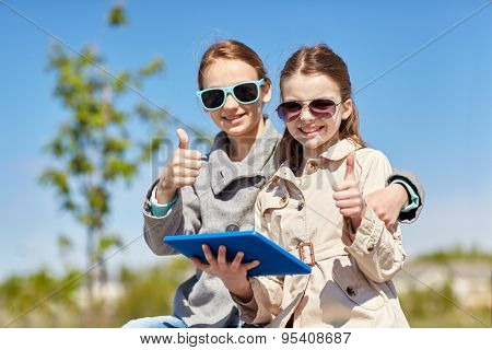 people, children, technology, friends and friendship concept - happy little girls in sunglasses with tablet pc computer showing thumbs up outdoors