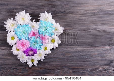 Beautiful flowers in heart shape on wooden background