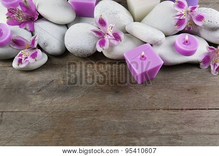 Spa still life with purple flowers, pebbles and candlelight on wooden background