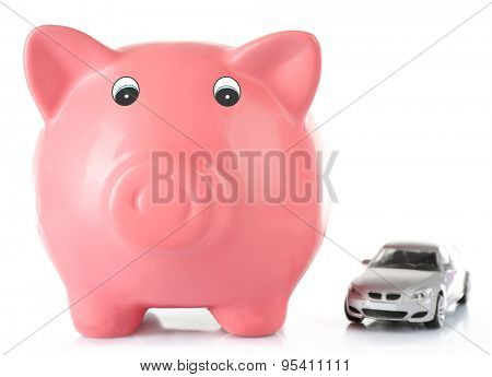Piggy bank with toy car isolated on white