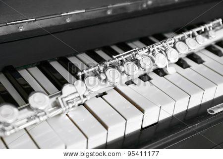 Flute on piano keys, closeup