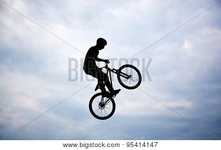 Silhouette of a man doing a jump with a bmx bike
