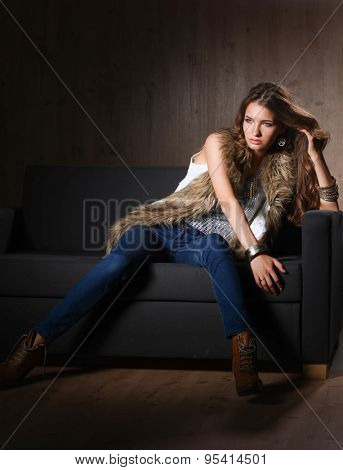 Portrait of a elegant woman sitting on a black sofa wearing a blue jeans and fur vest
