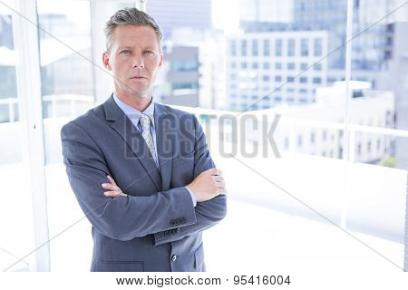 Thinking businessman looking at the camera in the office