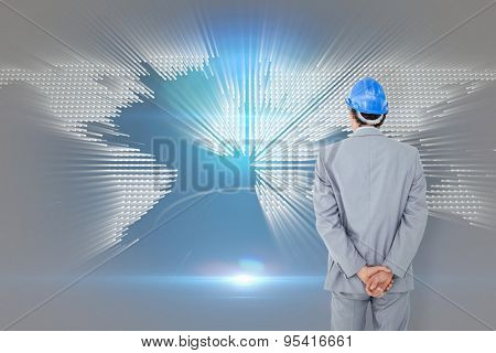 Businessman with helmet turning his back to camera against glowing world map on black background