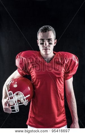 A serious american football player looking at camera with black background