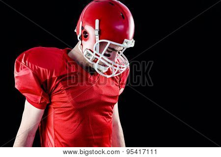 A football player taking his helmet on her head with blac background