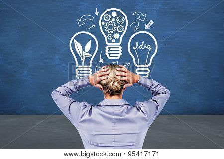 Rear view of worried businesswoman holding her head against blue room