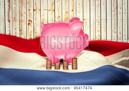 Coins and piggy bank against wooden background in pale wood