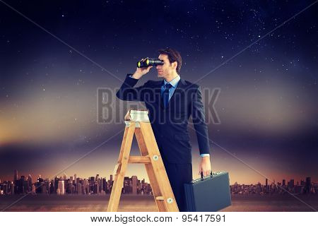 Businessman looking on a ladder against city on the horizon
