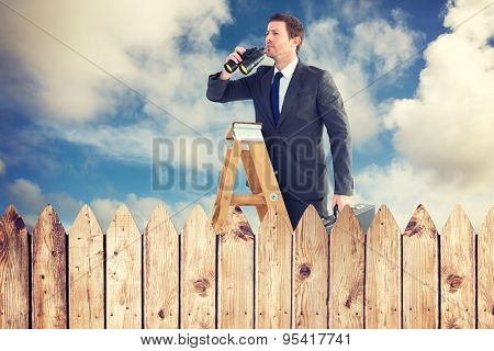 Businessman looking on a ladder against fence under blue sky