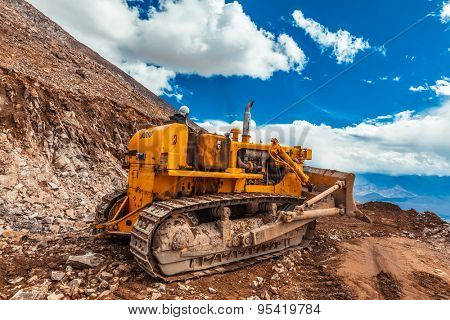 LADAKH, INDIA - SEPTEMBER 12, 2011: Bulldozer doing road constractuion on Kardung La pass in Himalayas. Ladakh, Jammu and Kashmir, India